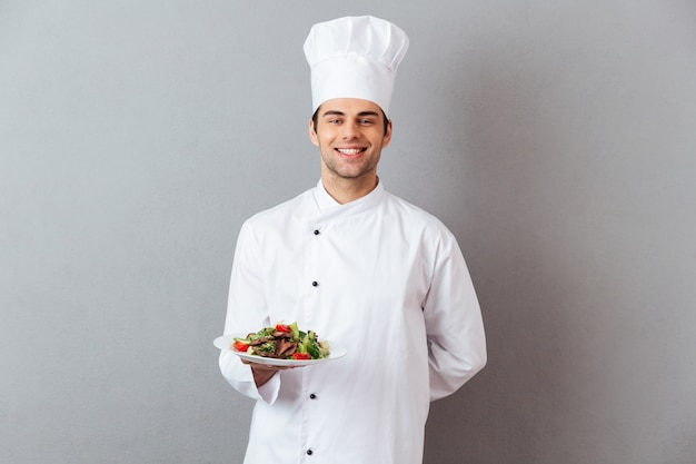 Happy young cook in uniform holding salad.