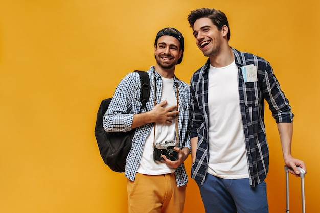 흰색 티셔츠와 체크 무늬 셔츠를 입은 행복한 젊은 멋진 brunet 남자는 기뻐하고 미소 짓고 주황색 벽에 포즈를 취합니다. 여행자는 배낭과 레트로 카메라를 들고 있습니다.