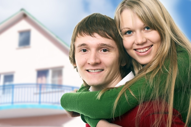 幸せな若いカップルと家