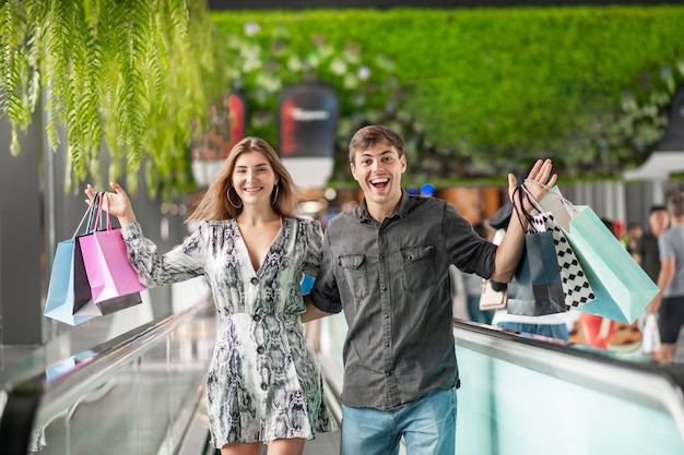 Happy young couple are standing embracing on an escalator holding packages with big purchases in their hands