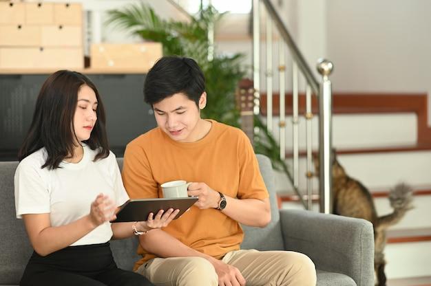 Счастливая молодая пара использует цифровой планшет дома, сидя на диване