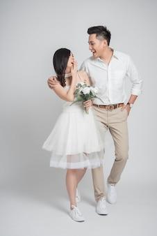 幸せな若いカップルアジアの新郎と新婦の白い背景で一緒に歩いて楽しんでカジュアルなウェディングドレスを着て