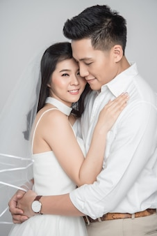 Happy young couple asian groom and bride in love wearing casual wedding dress embracing on white background