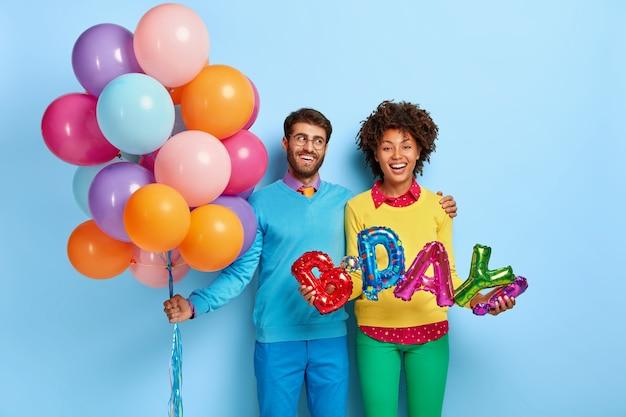 風船でポーズをとるパーティーで幸せな若いカップル