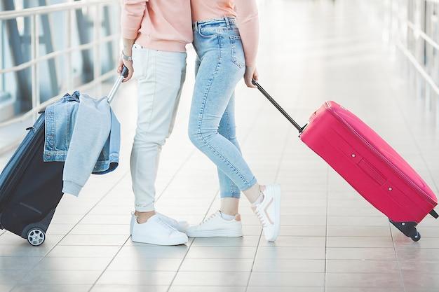 Счастливые молодые пары на крупном аэропорте имея потеху пока ждущ их полет. два человека, мужчина и женщина собирается в путешествие.
