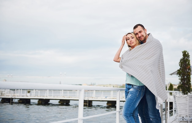 Happy young couple in a blanket, standing on the pier in the water.