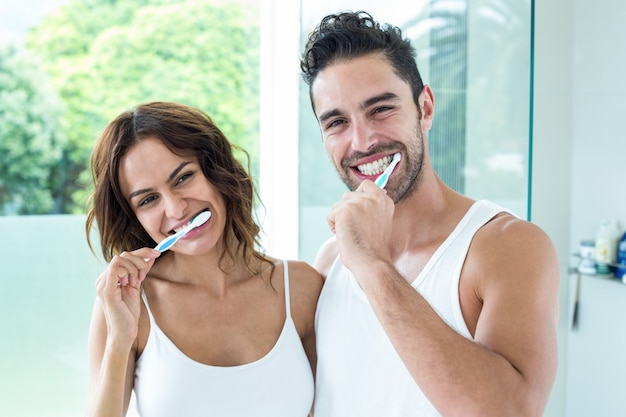 Happy young couple brushing teeth