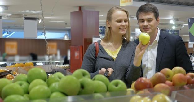 スーパーマーケットでリンゴを買う幸せな若いカップル