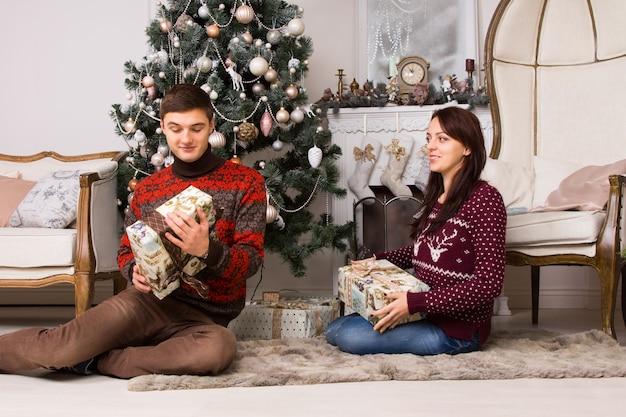贈り物を交換するクリスマスツリーの前に敷物の上に座ってクリスマスを祝う幸せな若いカップル