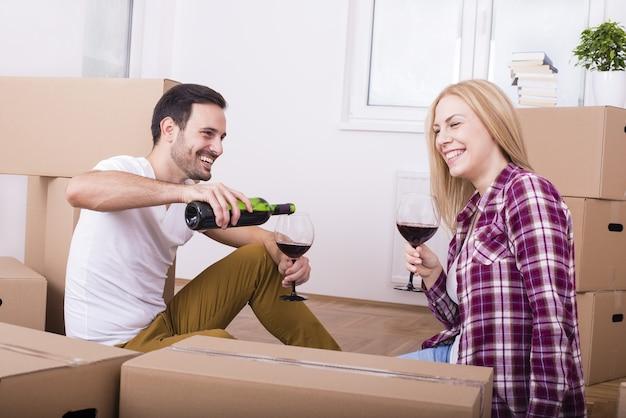 Счастливая молодая пара празднует переезд в новую квартиру