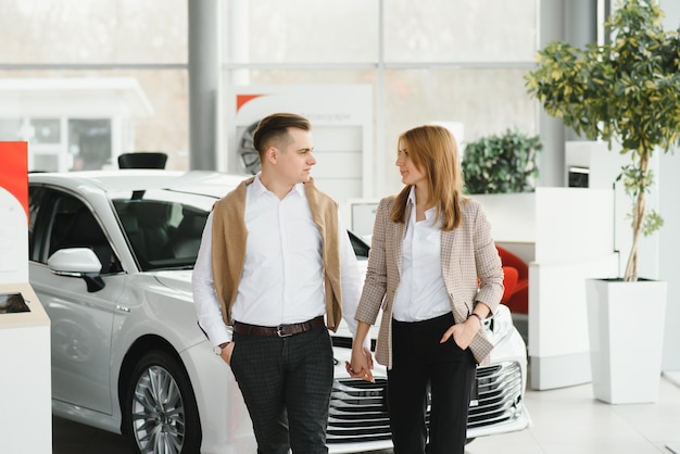 행복 한 젊은 부부는 대리점에서 가족을 위해 새 차를 선택하고 구입합니다.