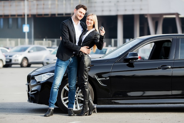 Happy young couple chooses and buying a new car for the family