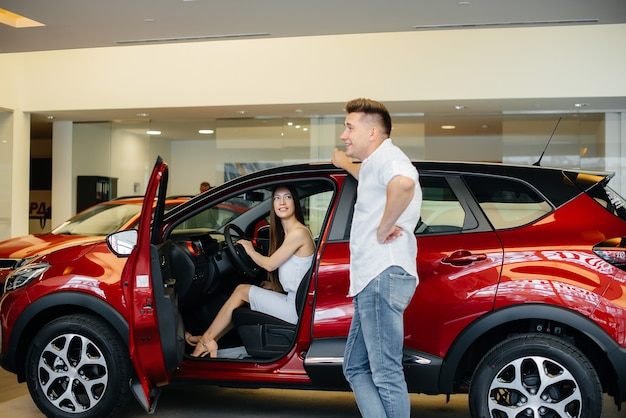 A happy young couple chooses and buys a new car at a car dealership. buying a new car.