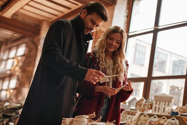 작은 거리 시장에서 수제 크리스마스 장식을 선택하는 행복한 젊은 커플