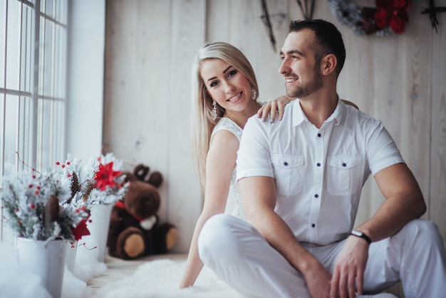 Happy young couple at christmas, beautiful gifts and tree in the