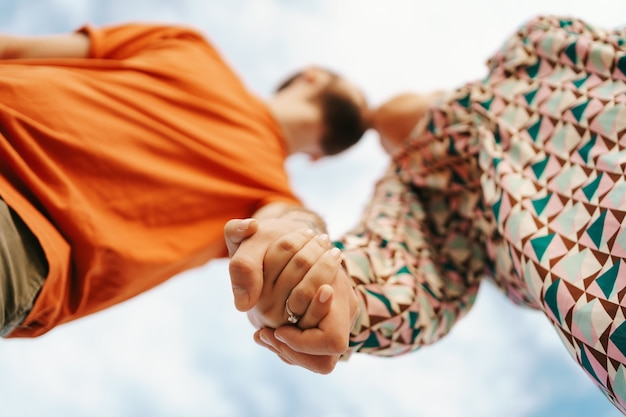 Happy young couple in colorful clothes with sky