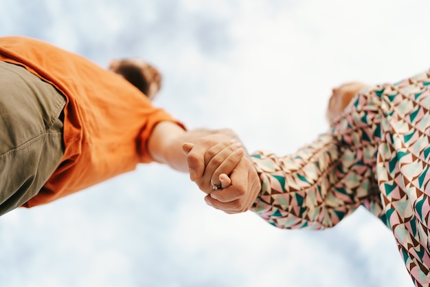 Felice giovane coppia in abiti colorati con il cielo