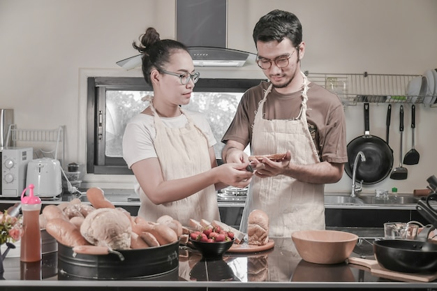 Happy young couple cooking in the kitchen, asian couple activity in kitchen.