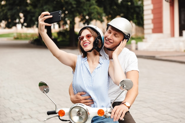 Happy young couple in crash helmets making selfie on smartphone while sitting together on scooter outdoors
