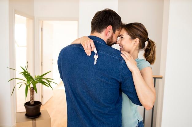 행복한 젊은 커플이 새 집에서 춤추고 움직이는 날을 축하합니다.