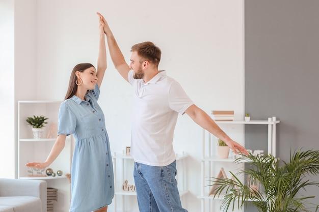 Счастливая молодая пара танцует дома