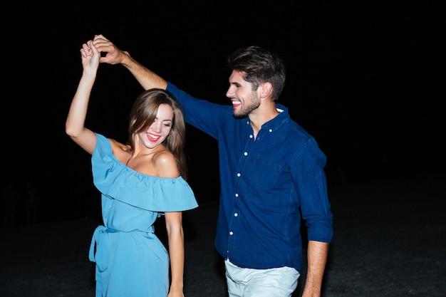 Счастливая молодая пара танцует вместе ночью