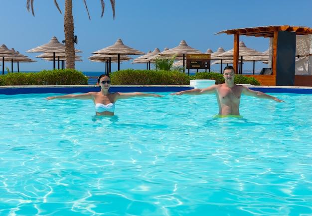 화창한 여름날 호텔 수영장에서 아쿠아 피트니스를 하는 행복한 젊은 커플