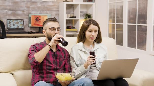 ラップトップでオンラインショッピングをしている幸せな若いカップル。ソファに座ってソーダを飲み、チップスを食べるカップル。