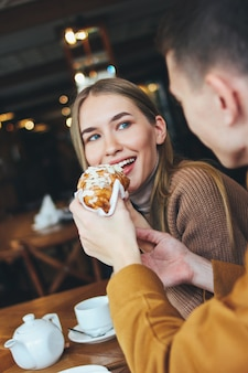 Happy young couple dressed warm casual clothing sitting at cafe together. the man feeds girl croissant