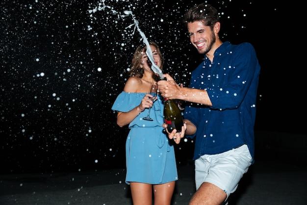 Счастливая молодая пара пьет шампанское и веселится ночью на пляже