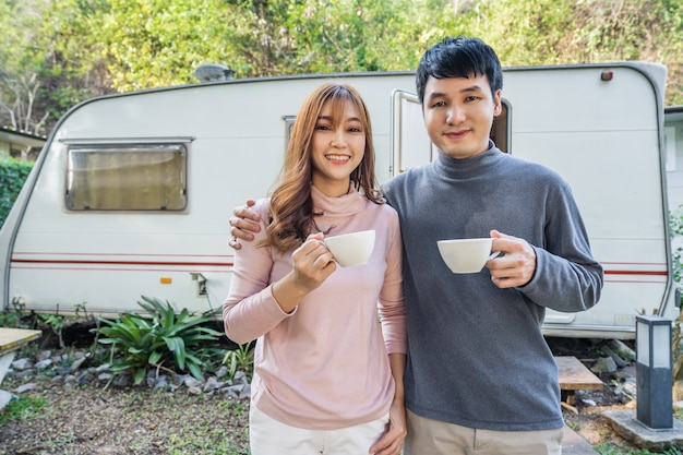 Happy young couple drinking coffee in front of a camper rv van motorhome