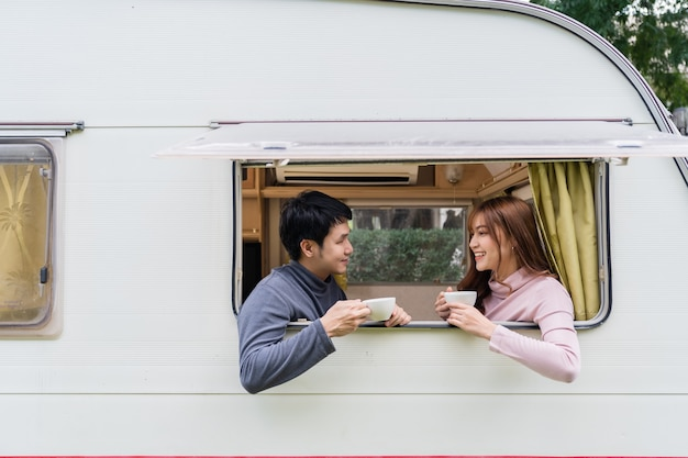 Happy young couple drinking coffee at window of a camper rv van motorhome