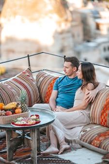 Счастливая молодая пара во время восхода солнца, наблюдая за воздушными шарами в каппадокии, турция