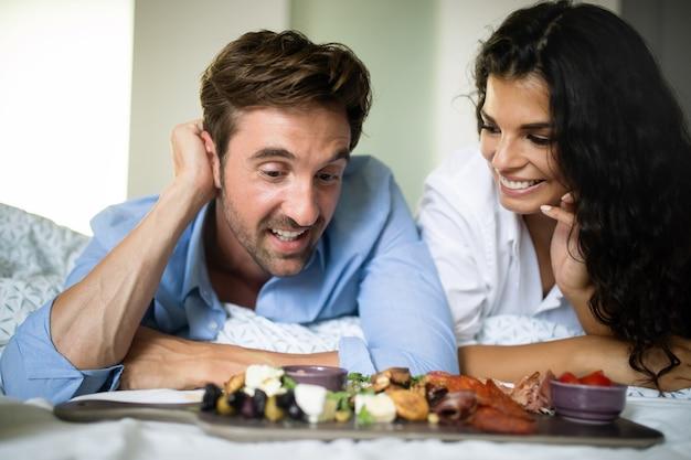 幸せな若いカップルは朝、ベッドで朝食を食べます。ベッドに横たわっている素敵なカップル