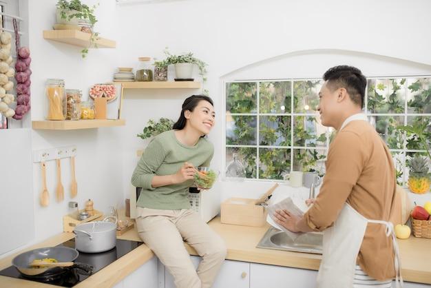 부엌에서 먹고 이야기하는 행복한 젊은 커플