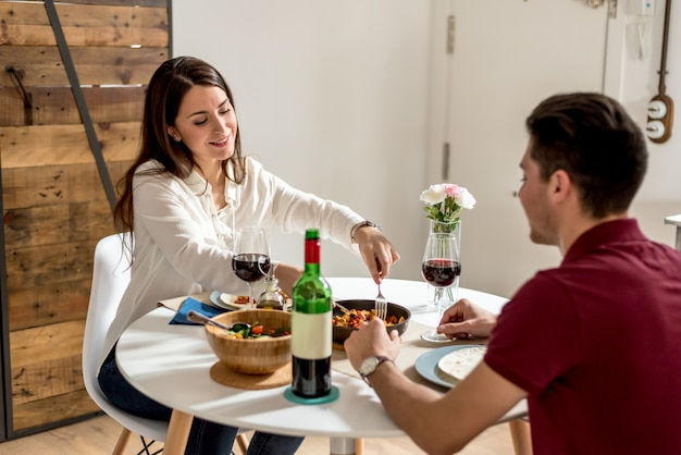 Happy young couple eating and drinking wine at home