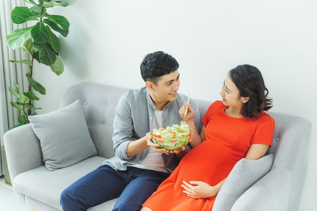 Happy young couple eating salad together at sofa in living room