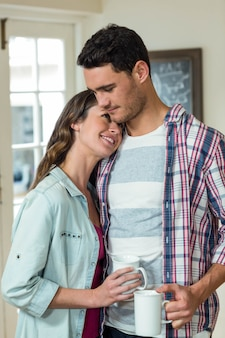 Happy young couple embracing each other and having a cup of coffee in kitchen