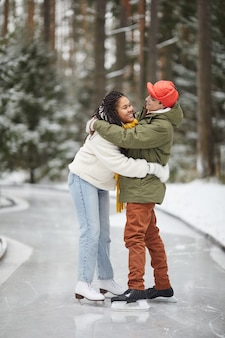 Happy young couple embracing each other standing on skating rink outdoors in winter