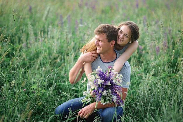 夏の草原を受け入れる幸せな若いカップル