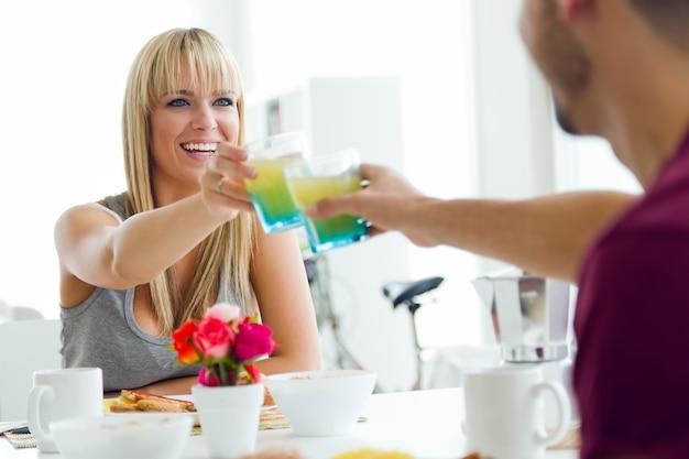 Счастливый молодая пара, наслаждаясь завтрак на кухне.