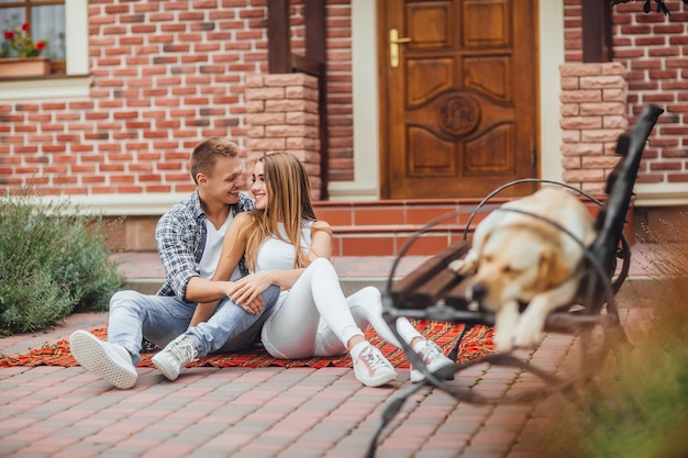 Happy young couple enjoying each other and sitting at the blanket carpet in front of the house. the dog is sleeping at the bench