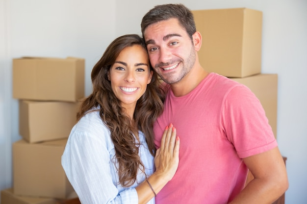 Happy young couple enjoying moving into new flat, standing among carton boxes, hugging and looking at camera