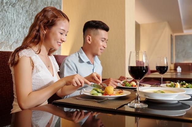 멋진 레스토랑에서 맛있는 저녁 식사를 즐기는 행복한 젊은 커플