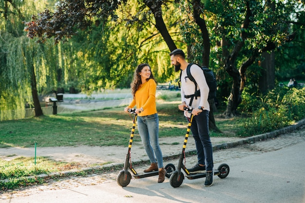 Happy young couple enjoying together while riding electric scooters in city park.