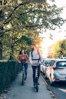 도시 공원에서 전기 스쿠터를 타고 함께 즐기는 행복한 젊은 커플.