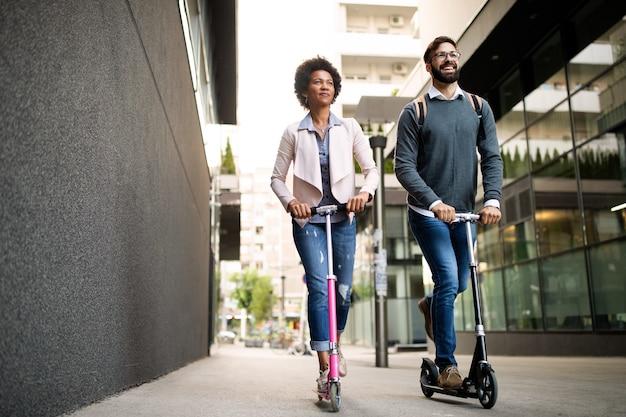 Счастливая молодая пара, наслаждаясь вместе во время езды на электрических скутерах на городской улице
