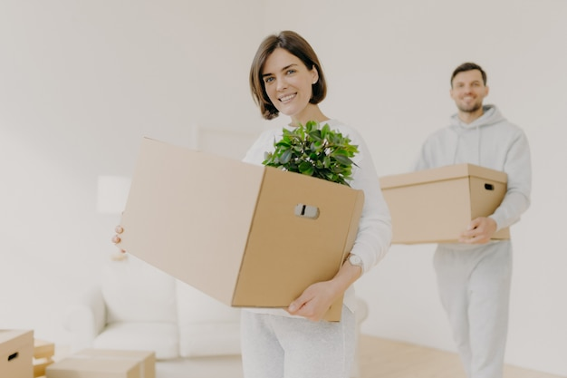 Happy young couple enter own modern house, buy real estate, carry cardboard boxes with indoor plant
