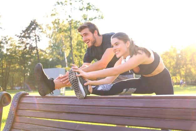 공원에서 함께 운동하는 행복한 젊은 커플, 스트레칭 운동.