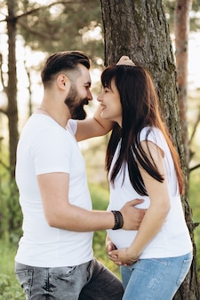 Happy young couple expecting baby in summer park